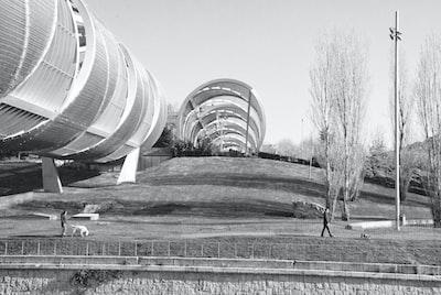 Grayscale photo of round building. People walking dogs under tubular bridge, black and white