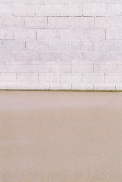 White wall tiles beside white wall. Water and brick texture