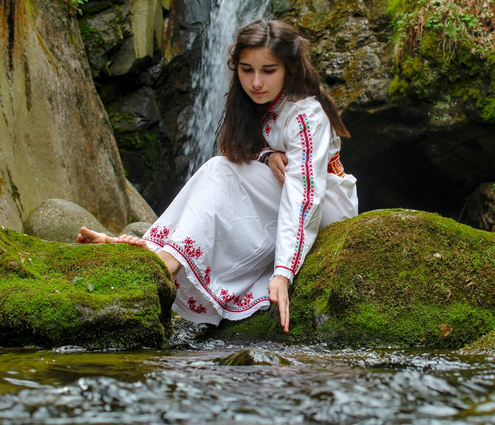 woman in white long sleeve dress sitting on rock by the river during daytime