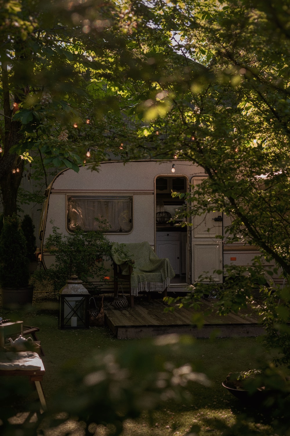white and green rv trailer under green tree during daytime