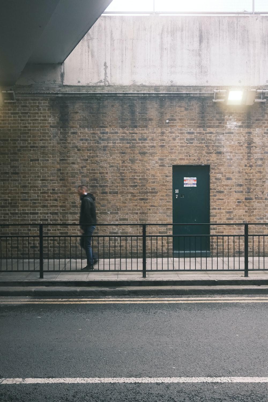 man in black coat standing on sidewalk during daytime