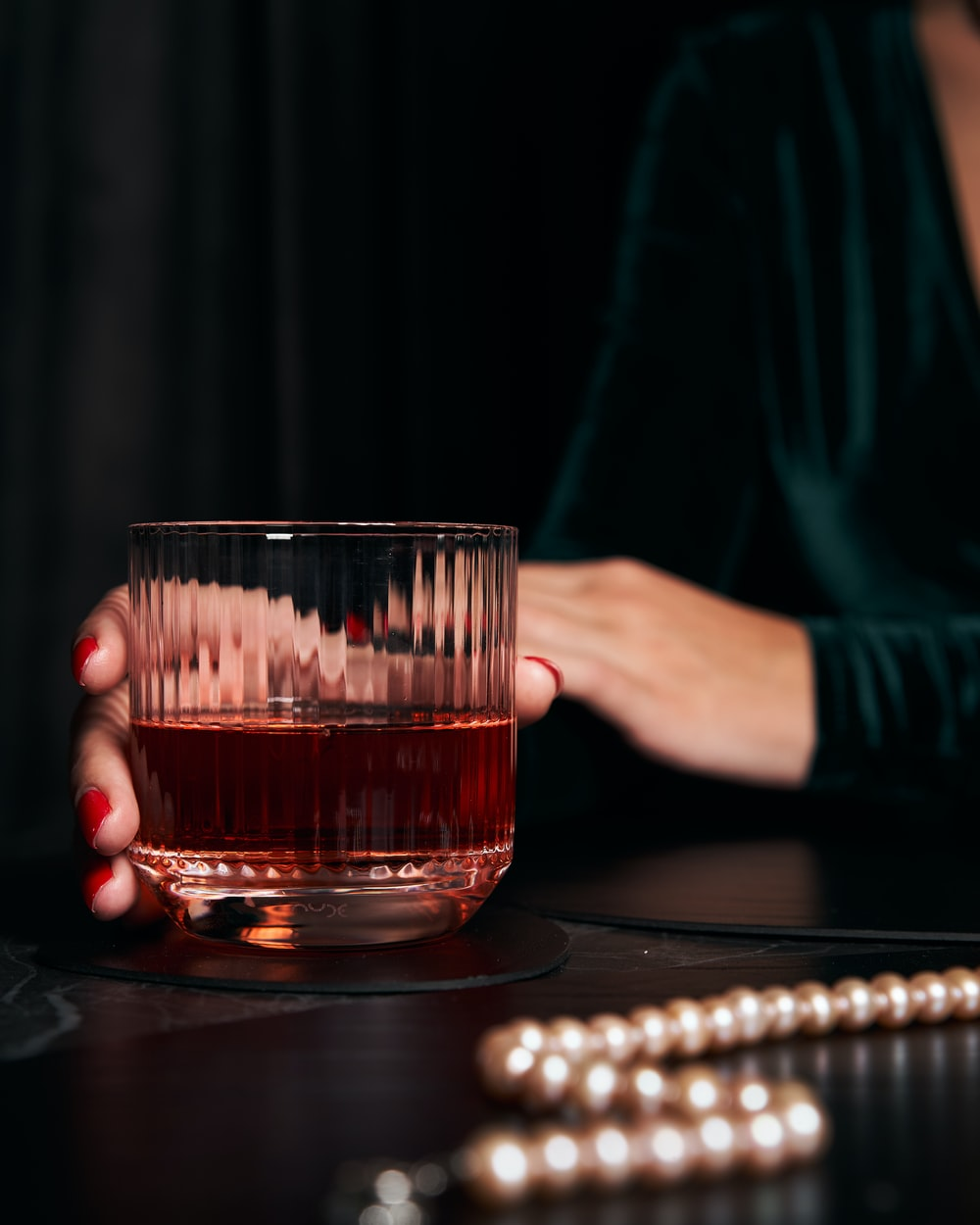 person holding clear drinking glass with red liquid