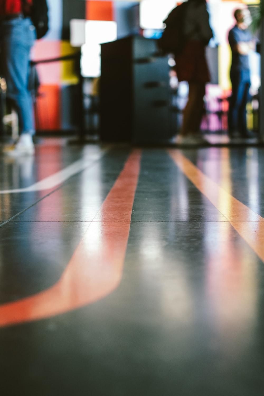 people walking on blue and orange floor tiles