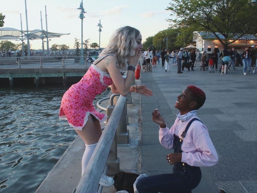 girl in pink dress standing beside man in white dress shirt