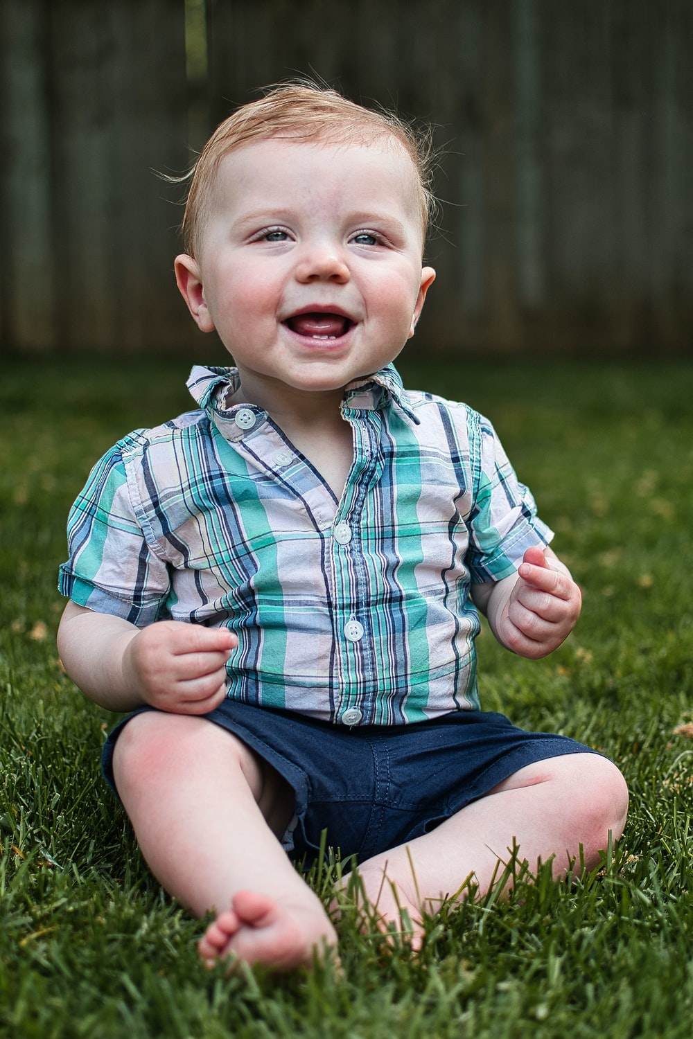 child in red white and blue plaid button up shirt and blue denim shorts sitting on on on on on