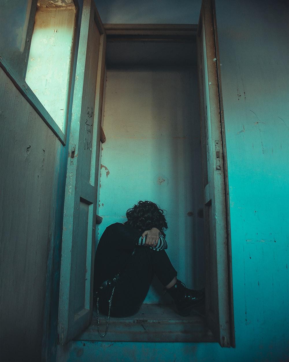 man in black jacket sitting on doorway