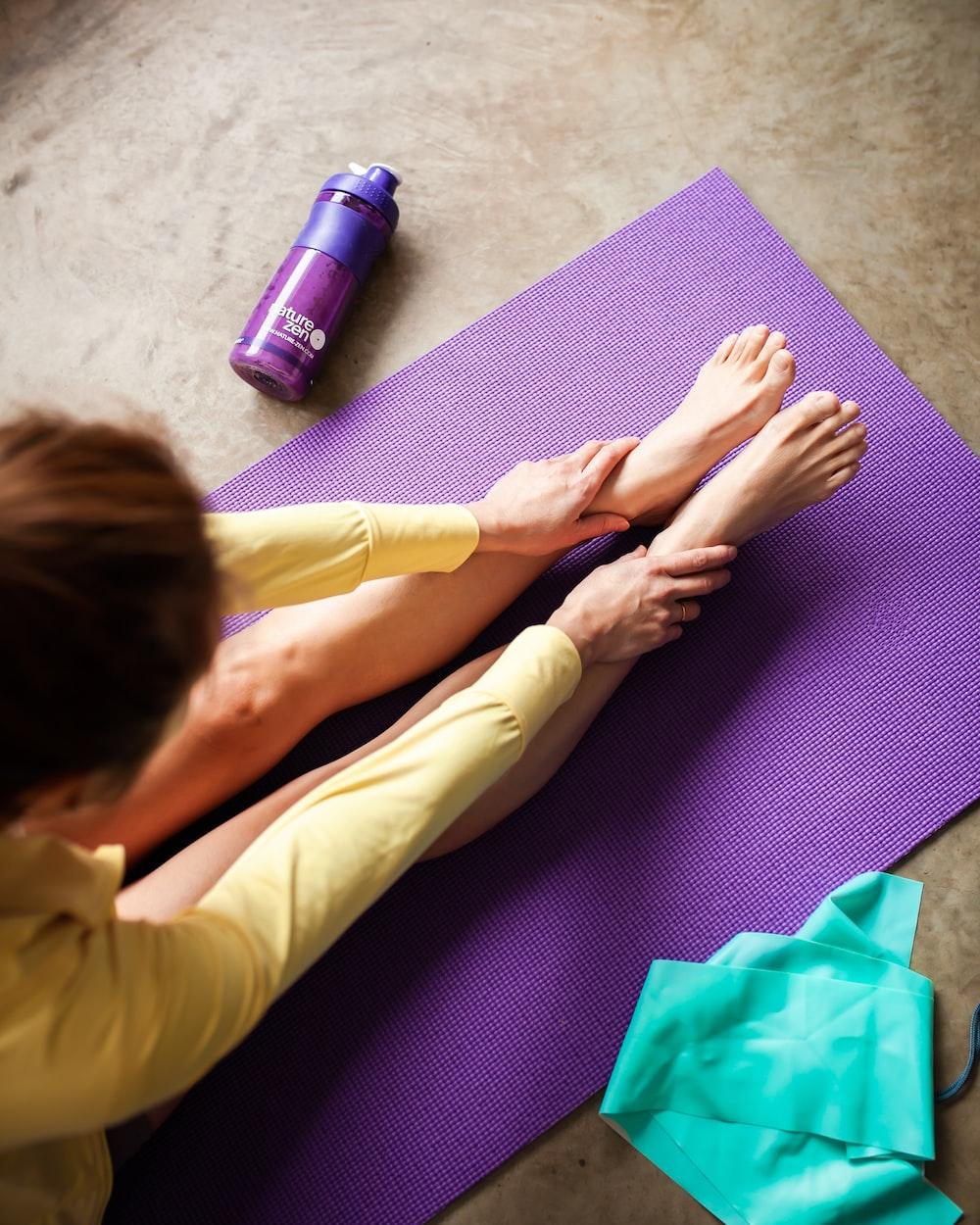woman in yellow pants lying on purple textile