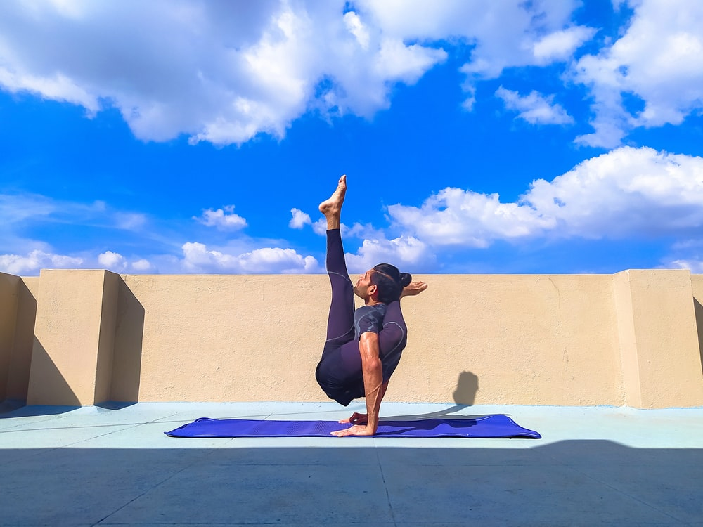woman in black tank top and black shorts doing yoga on blue yoga mat