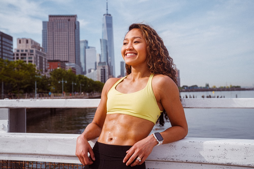 woman in yellow sports bra and black shorts standing near body of water during daytime