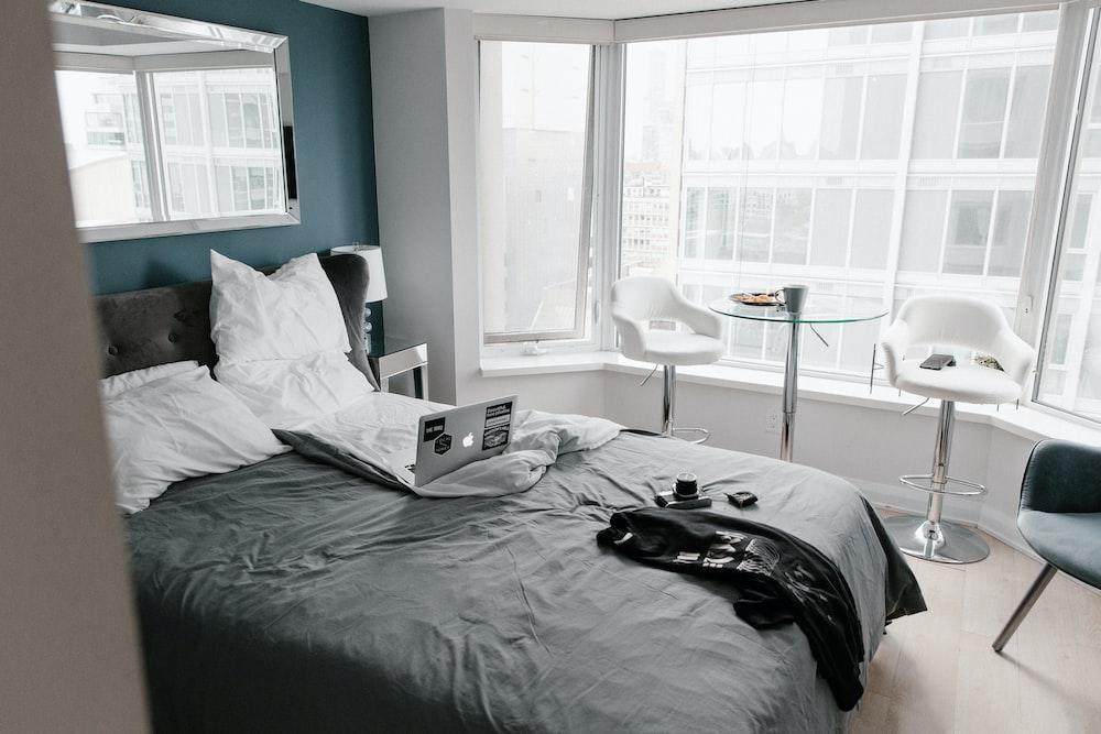 black bed linen near white wooden table