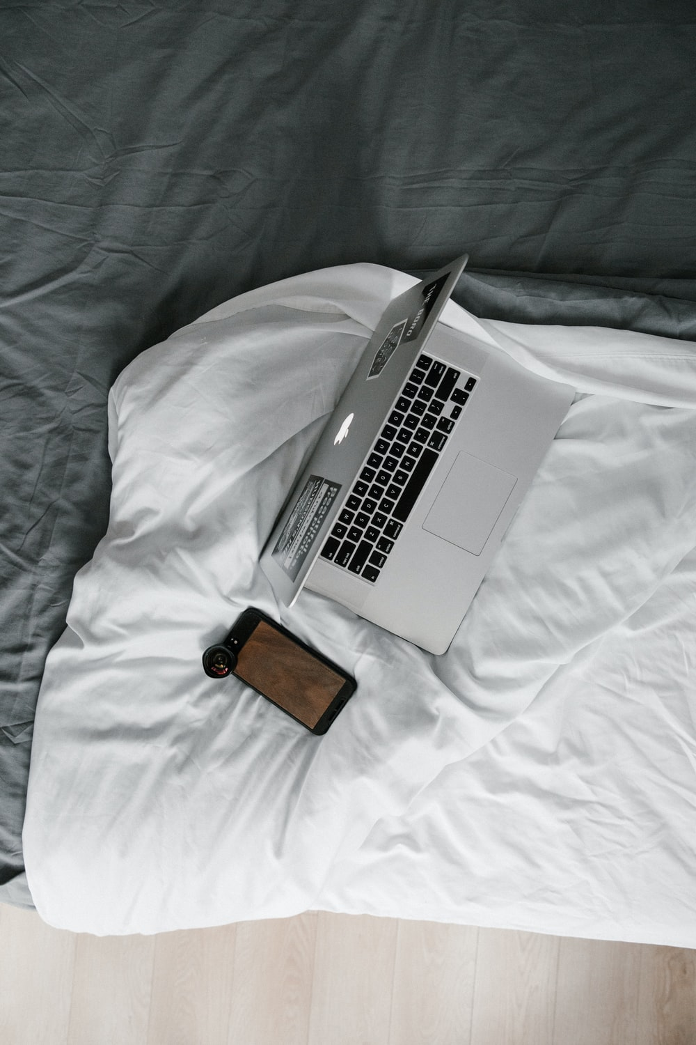 macbook pro beside brown leather wallet on white bed