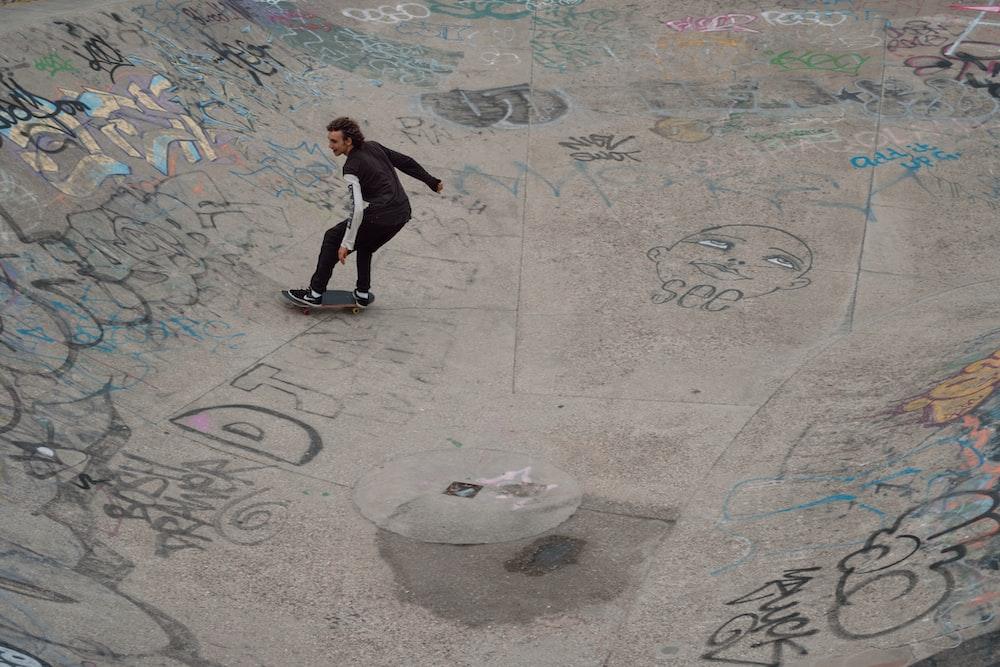 man in black suit standing on gray concrete floor