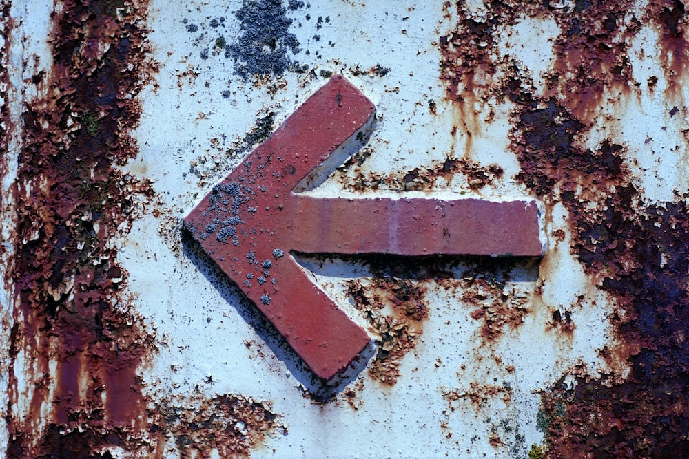 red arrow sign on white and brown concrete wall