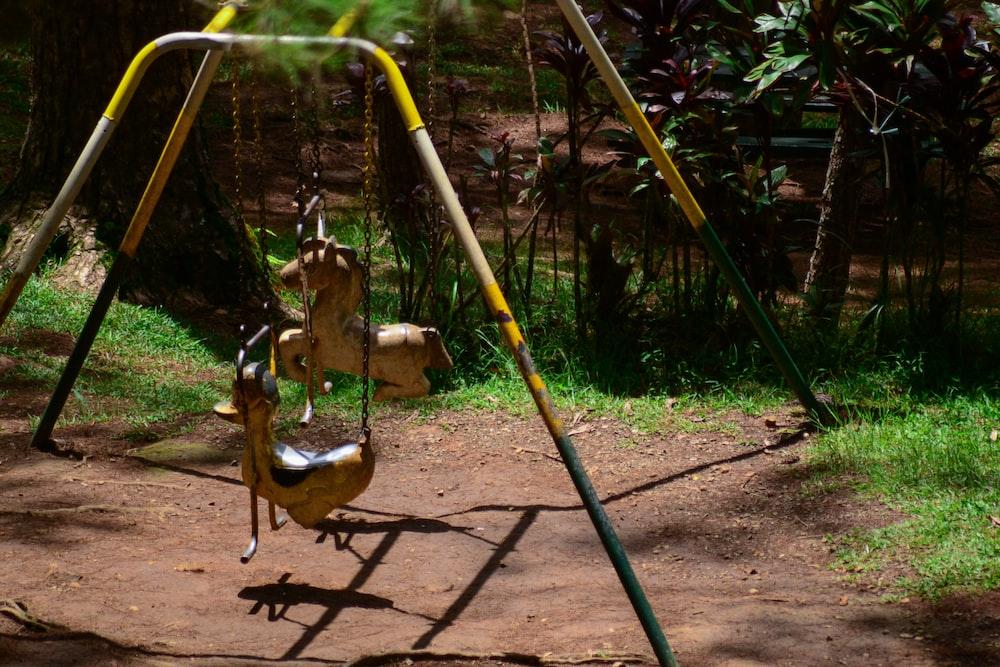 girl in yellow swing during daytime