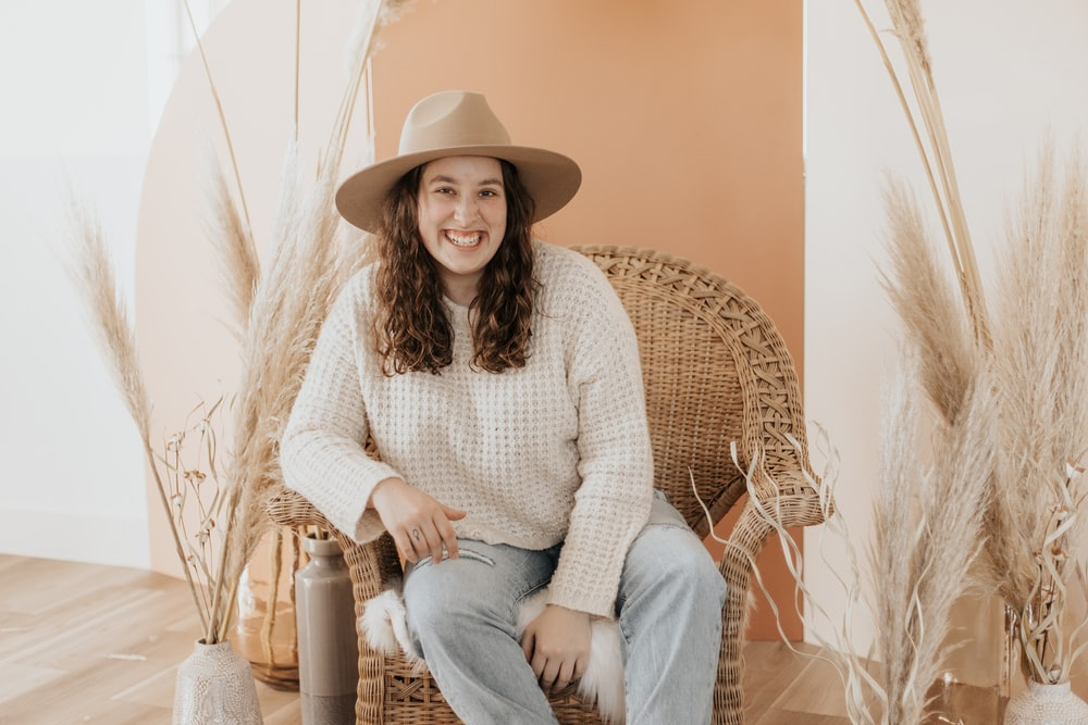 woman in white knit sweater and blue denim jeans sitting on brown wicker chair
