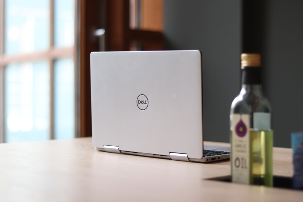 silver macbook beside white labeled bottle on table