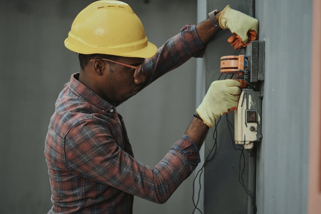 Portrait of a black man architect at a building site looking at camera. Confident civil engineering wearing a hardhat and eye goggles. Successful mature civil engineer at a construction site with open