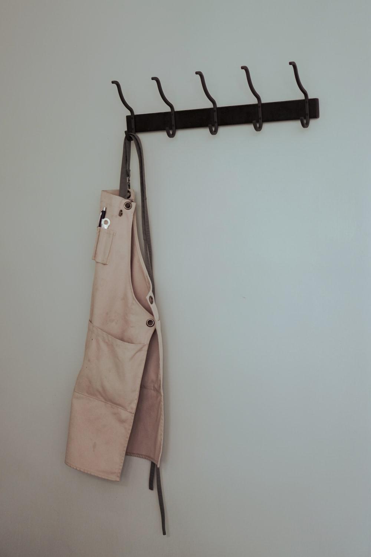 brown leather sling bag hanged on black clothes hanger