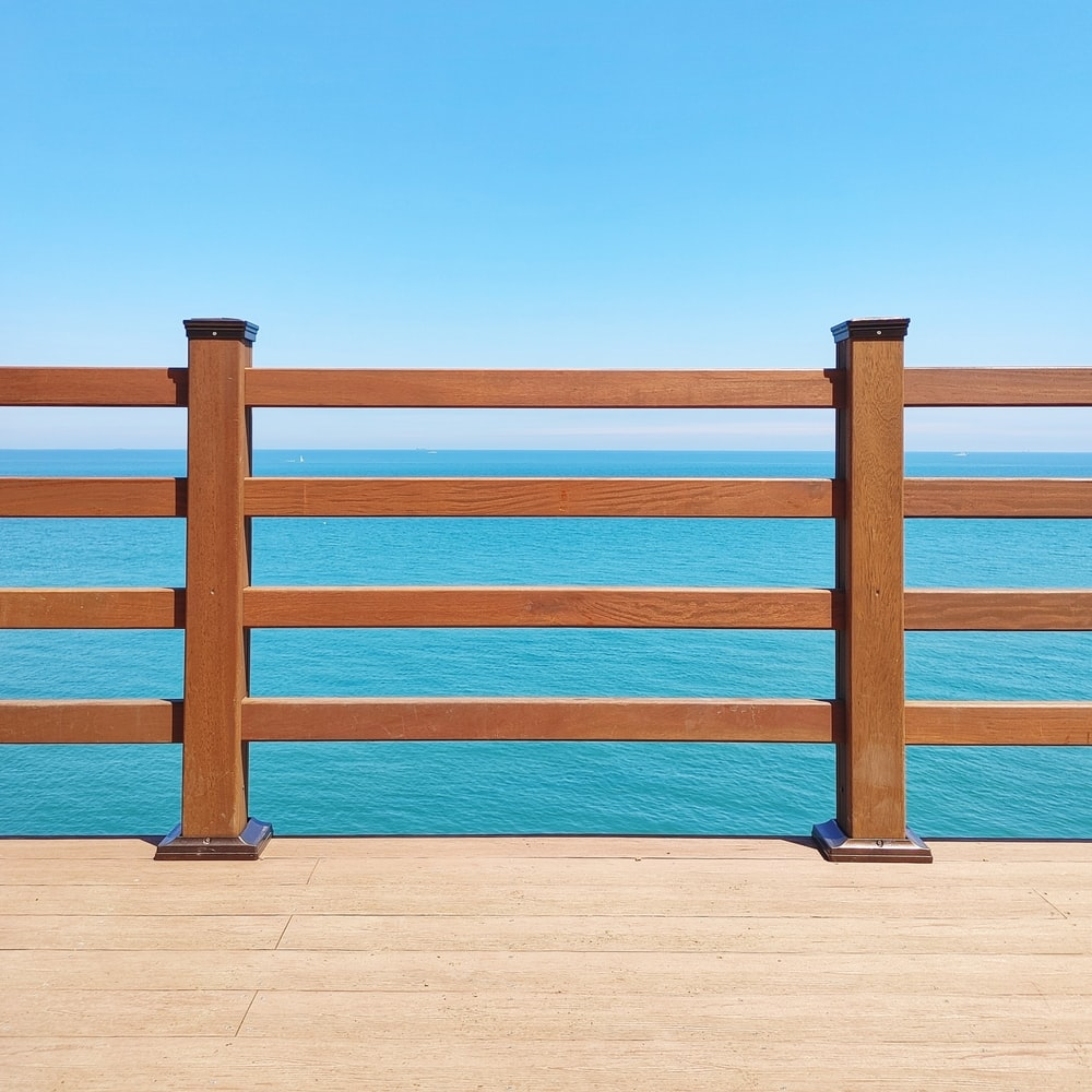 brown wooden fence on brown sand during daytime