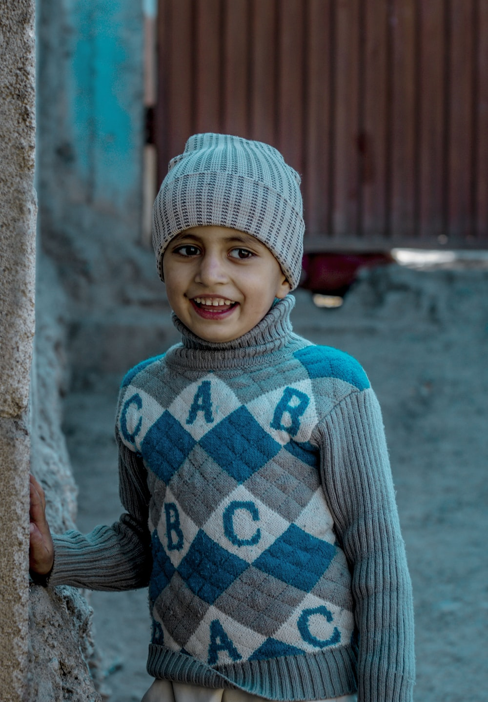 girl in blue and white striped sweater and pink knit cap