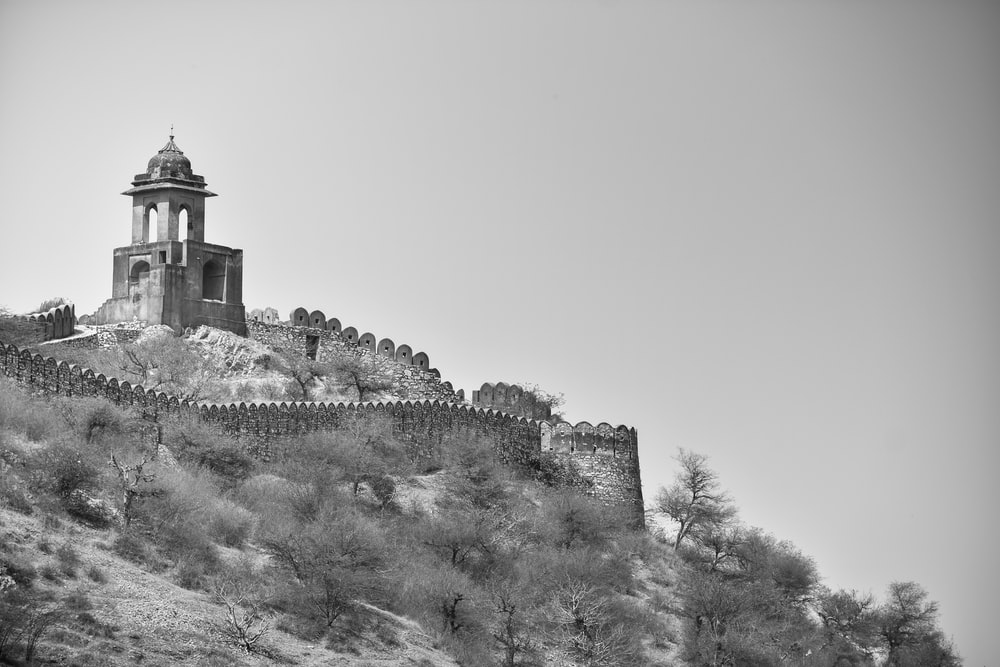 grayscale photo of castle on hill