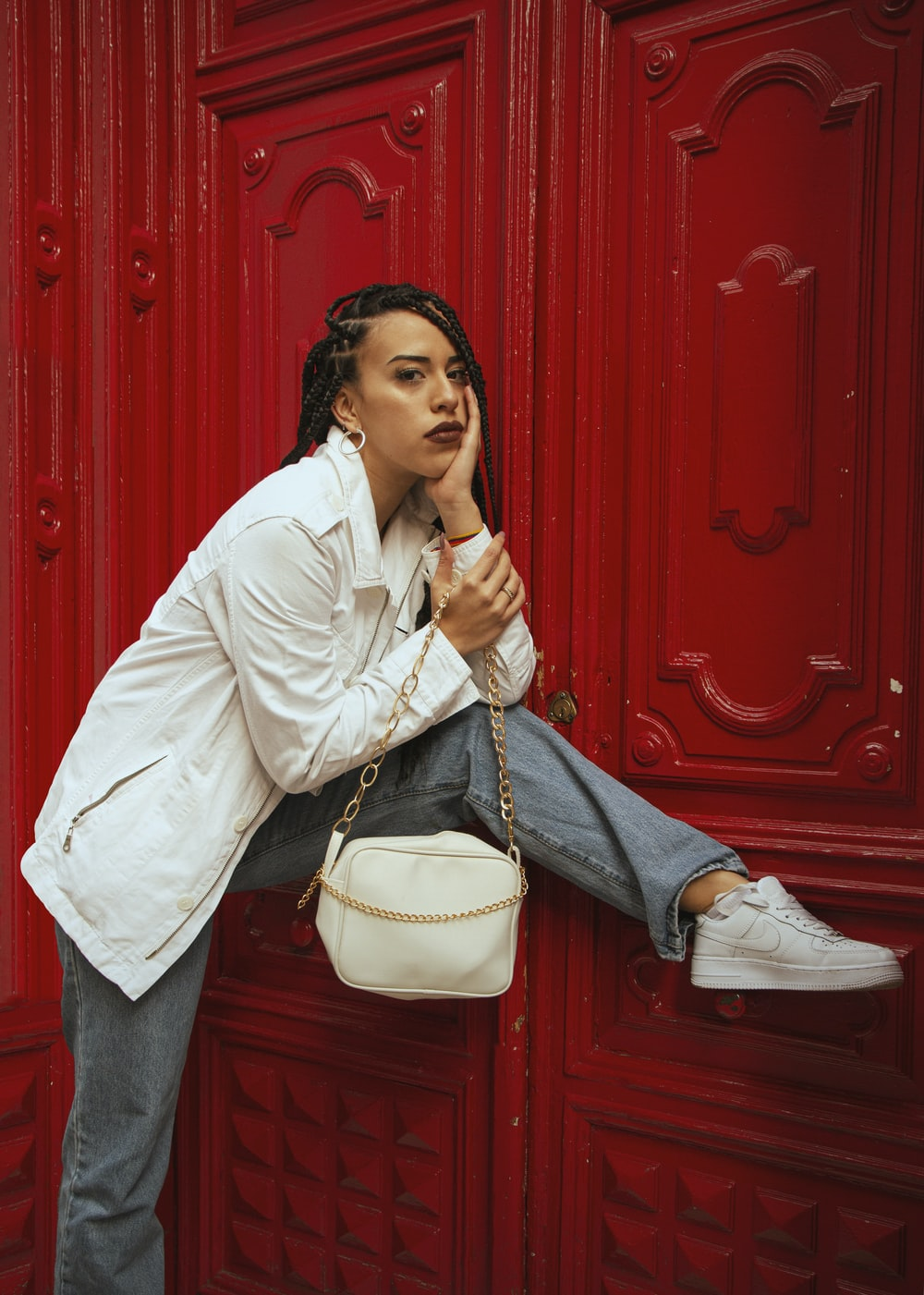 woman in white dress shirt and blue denim jeans sitting on red wooden door