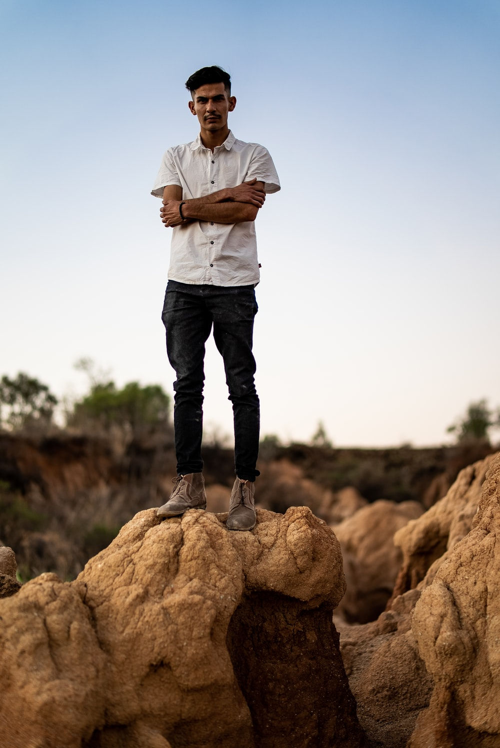 man in white dress shirt and black pants standing on brown rock during daytime