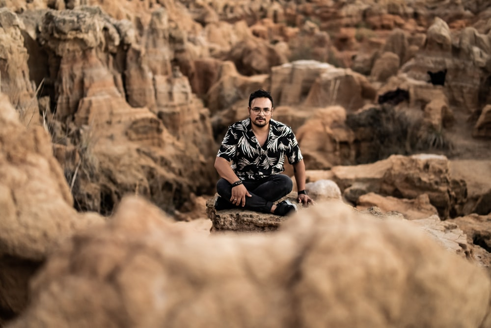 man in black and white checkered button up shirt sitting on brown rock during daytime