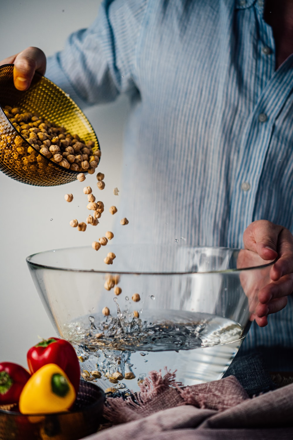 person holding clear glass bowl with corn