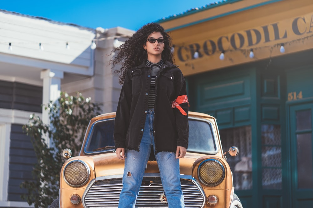 woman in black jacket and blue denim jeans standing beside yellow and silver vintage car during