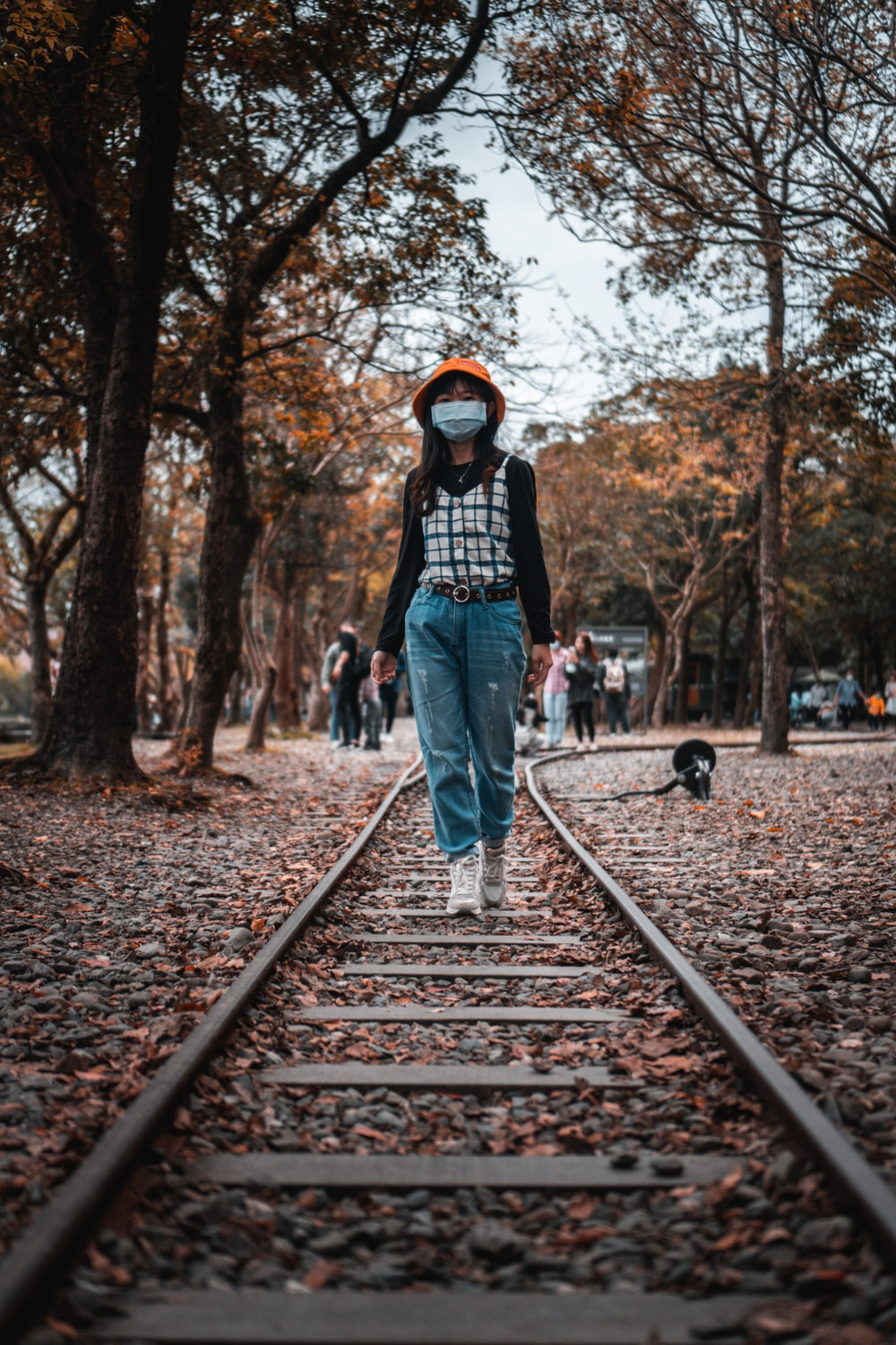 woman in black jacket and blue denim jeans standing on train rail during daytime