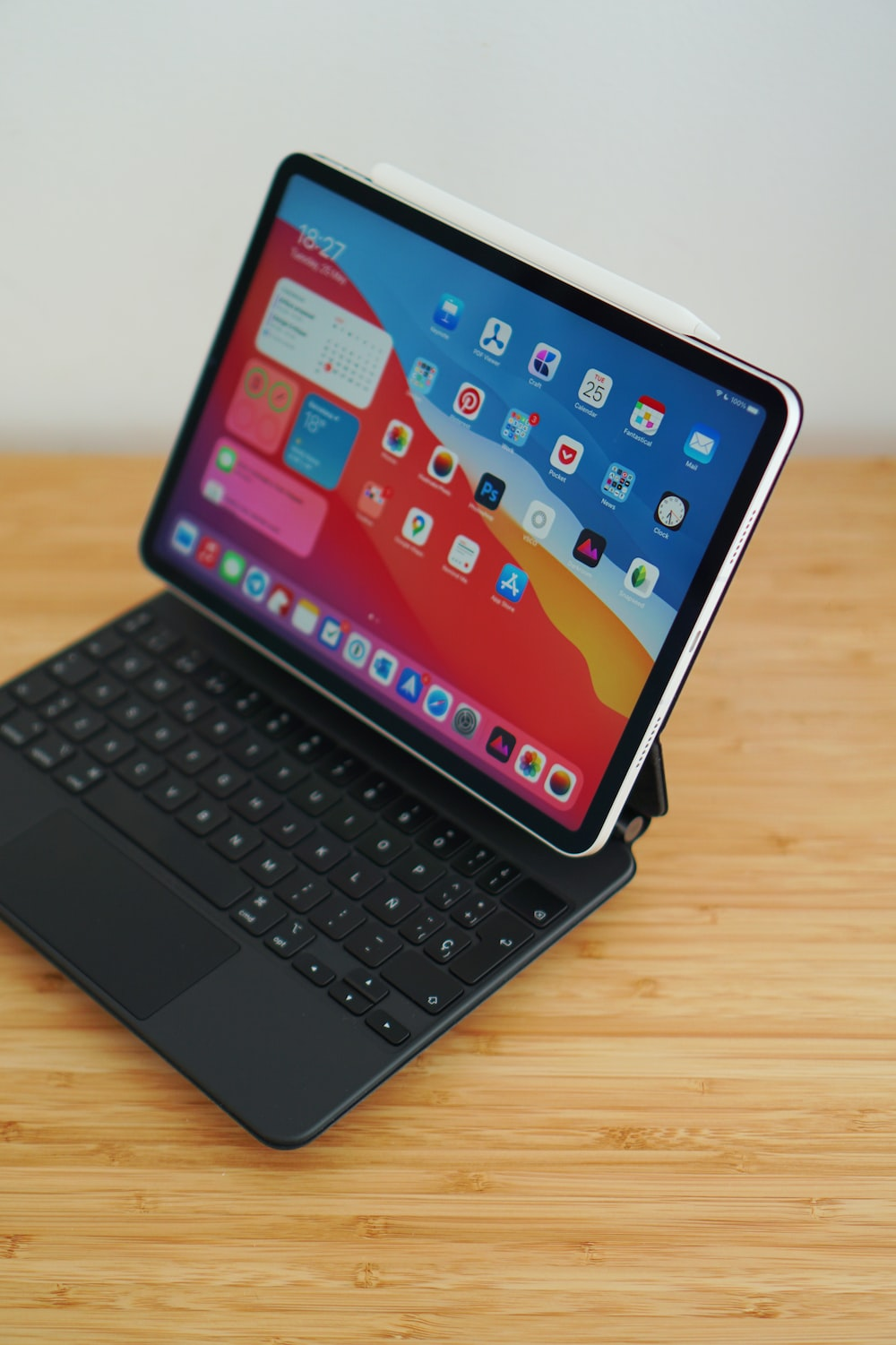 black ipad with keyboard on brown wooden table