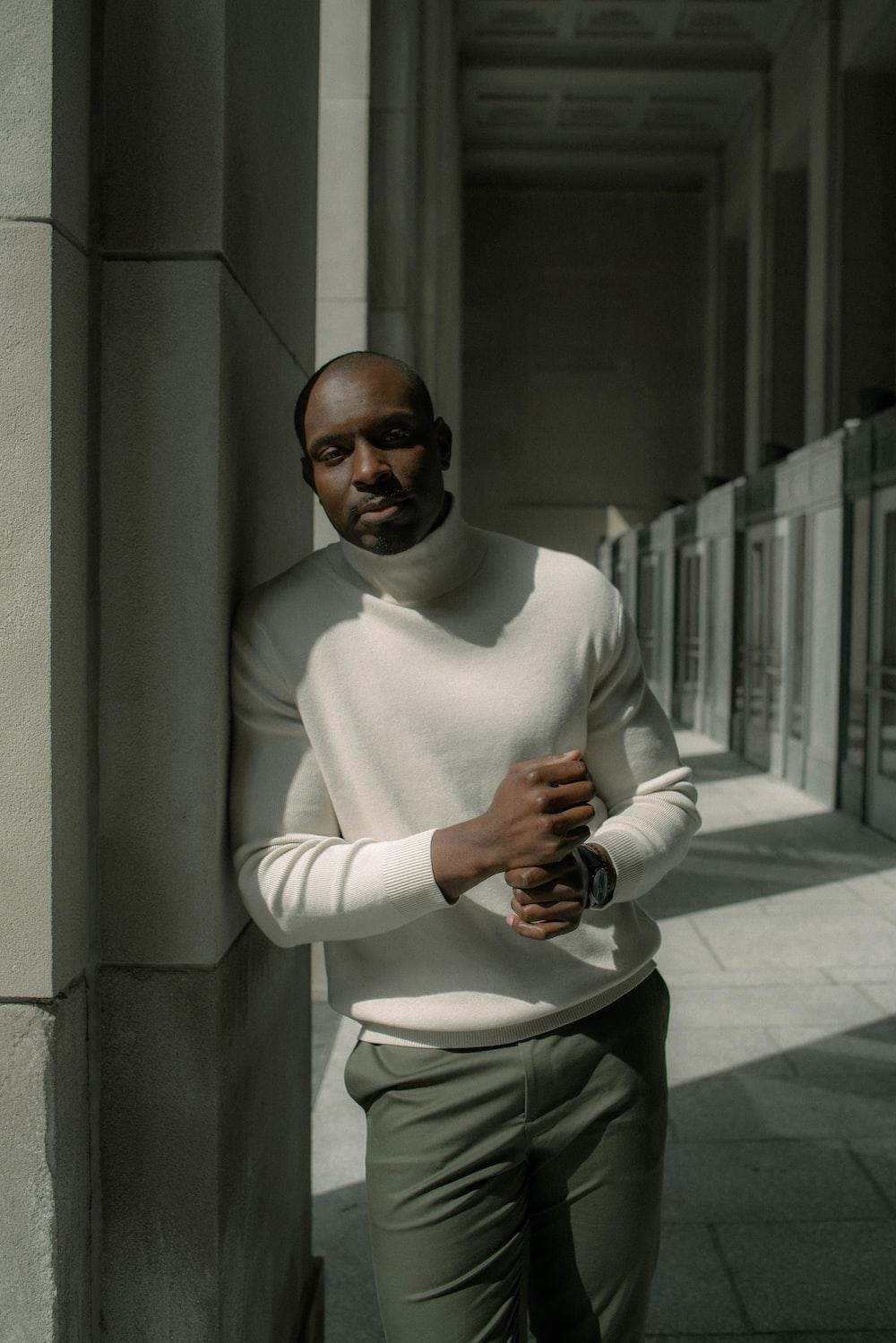 man in white turtleneck sweater holding black camera