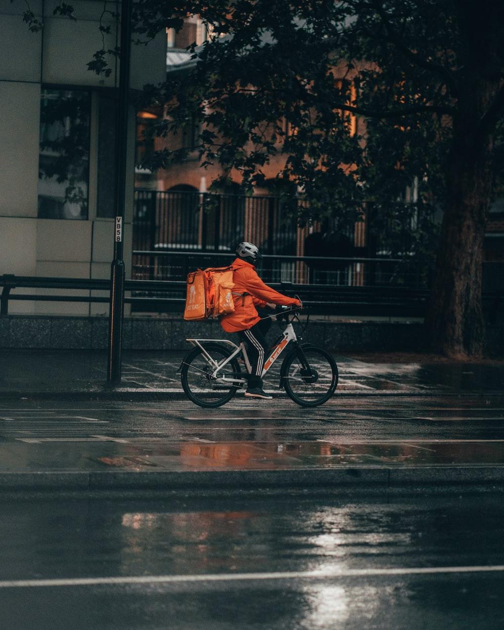 man in orange jacket riding bicycle on street during nighttime