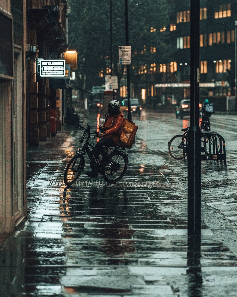 person in black jacket riding bicycle on sidewalk during daytime