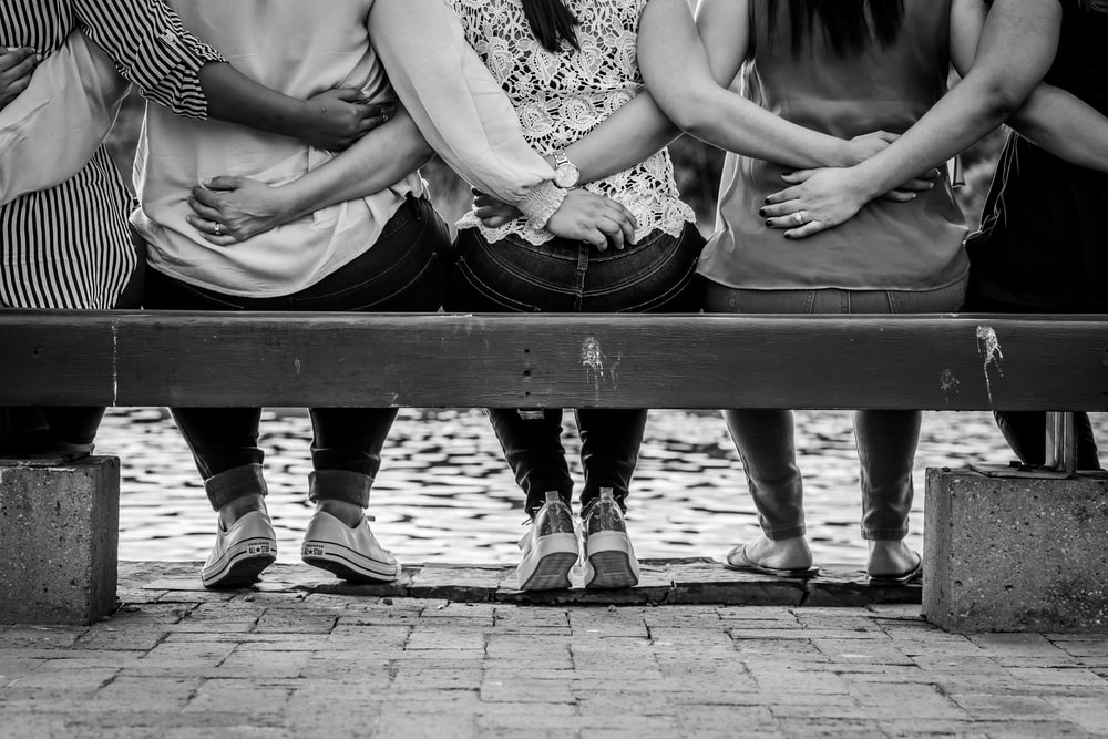 grayscale photo of 3 women sitting on wooden bench