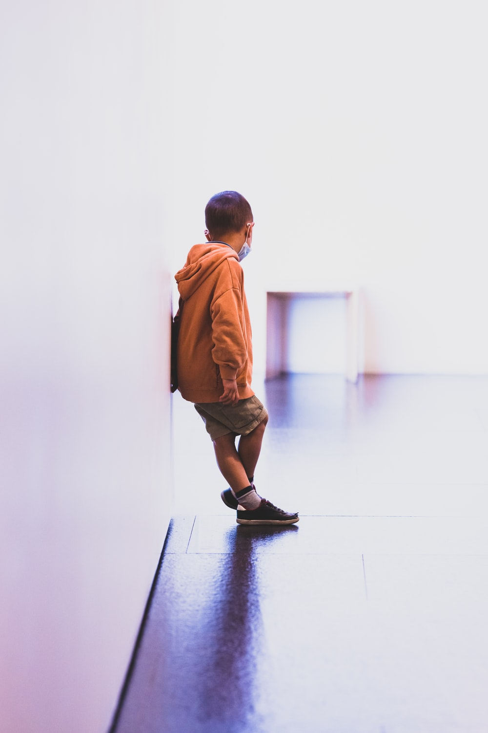 boy in brown long sleeve shirt and brown shorts standing on black floor
