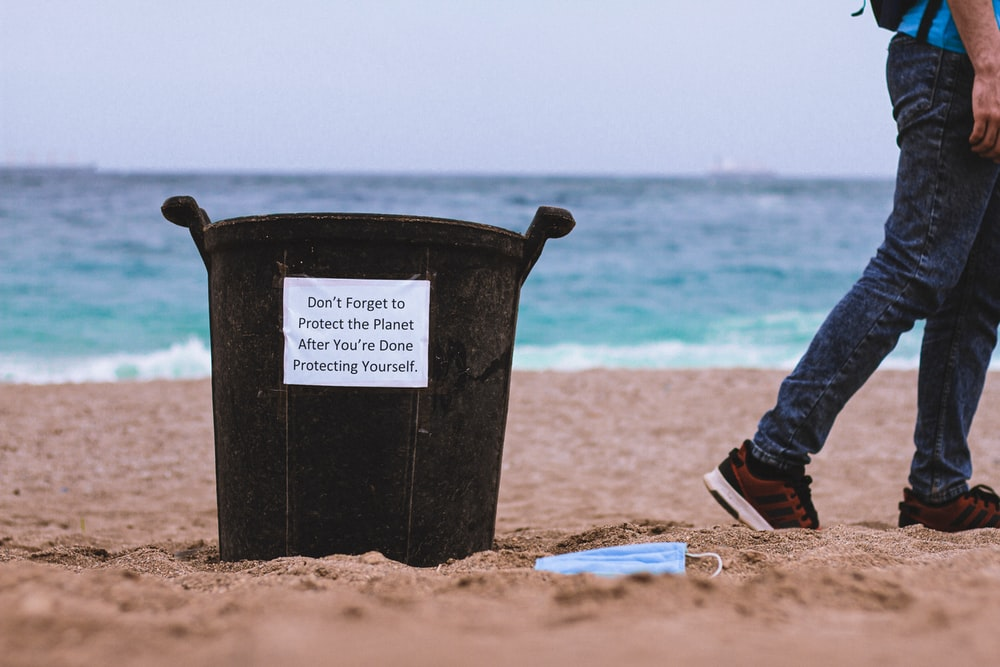 black plastic bucket on brown sand near body of water during daytime