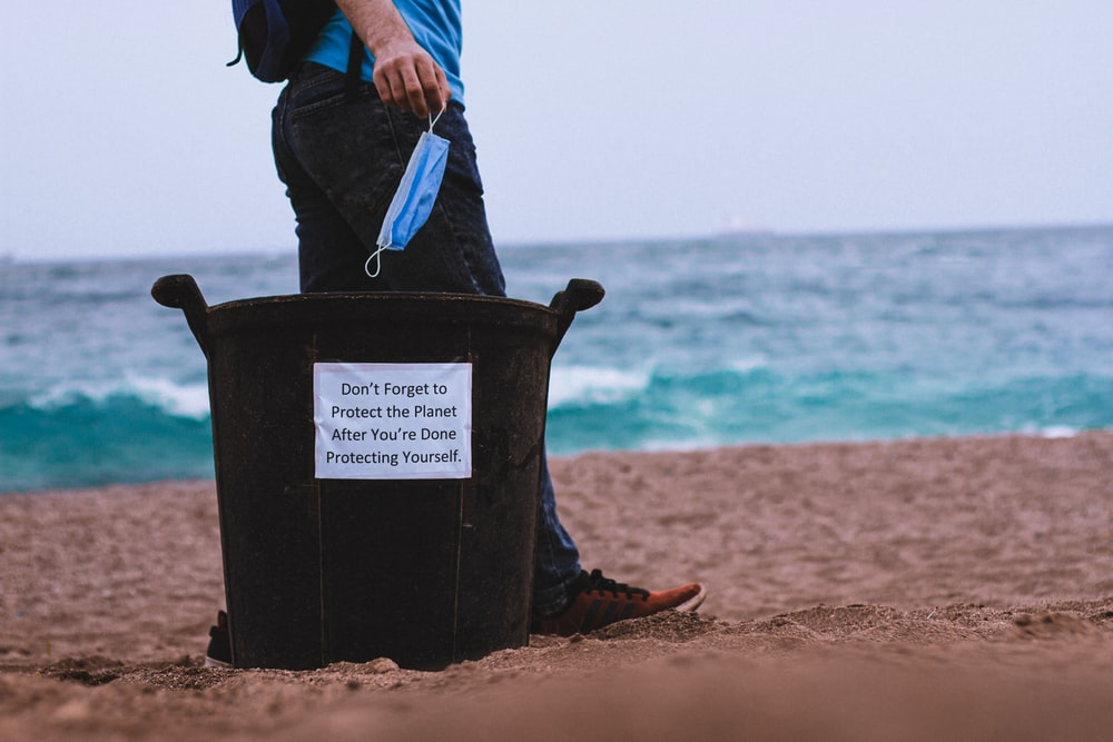 person in black jacket holding blue plastic bucket on beach during daytime
