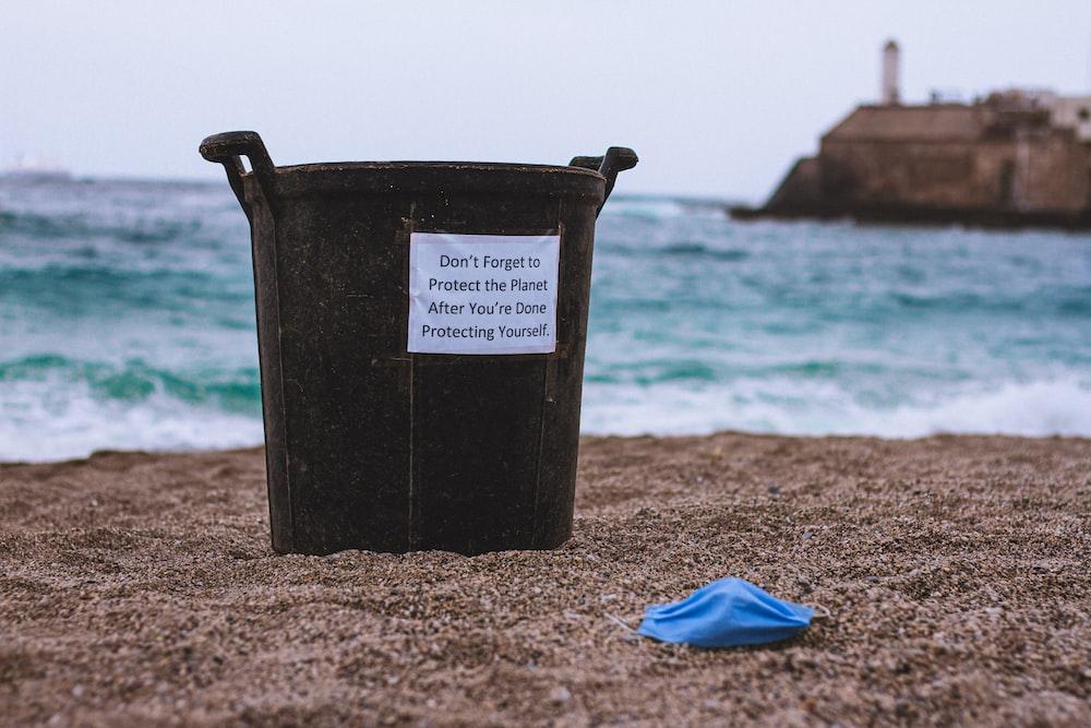 black plastic bucket on brown sand near blue textile during daytime
