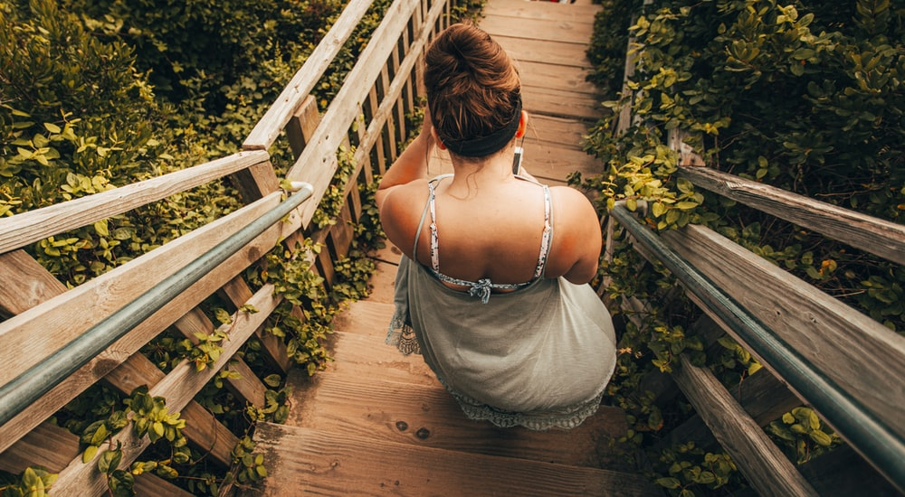 woman in white spaghetti strap top standing on brown wooden bridge during daytime