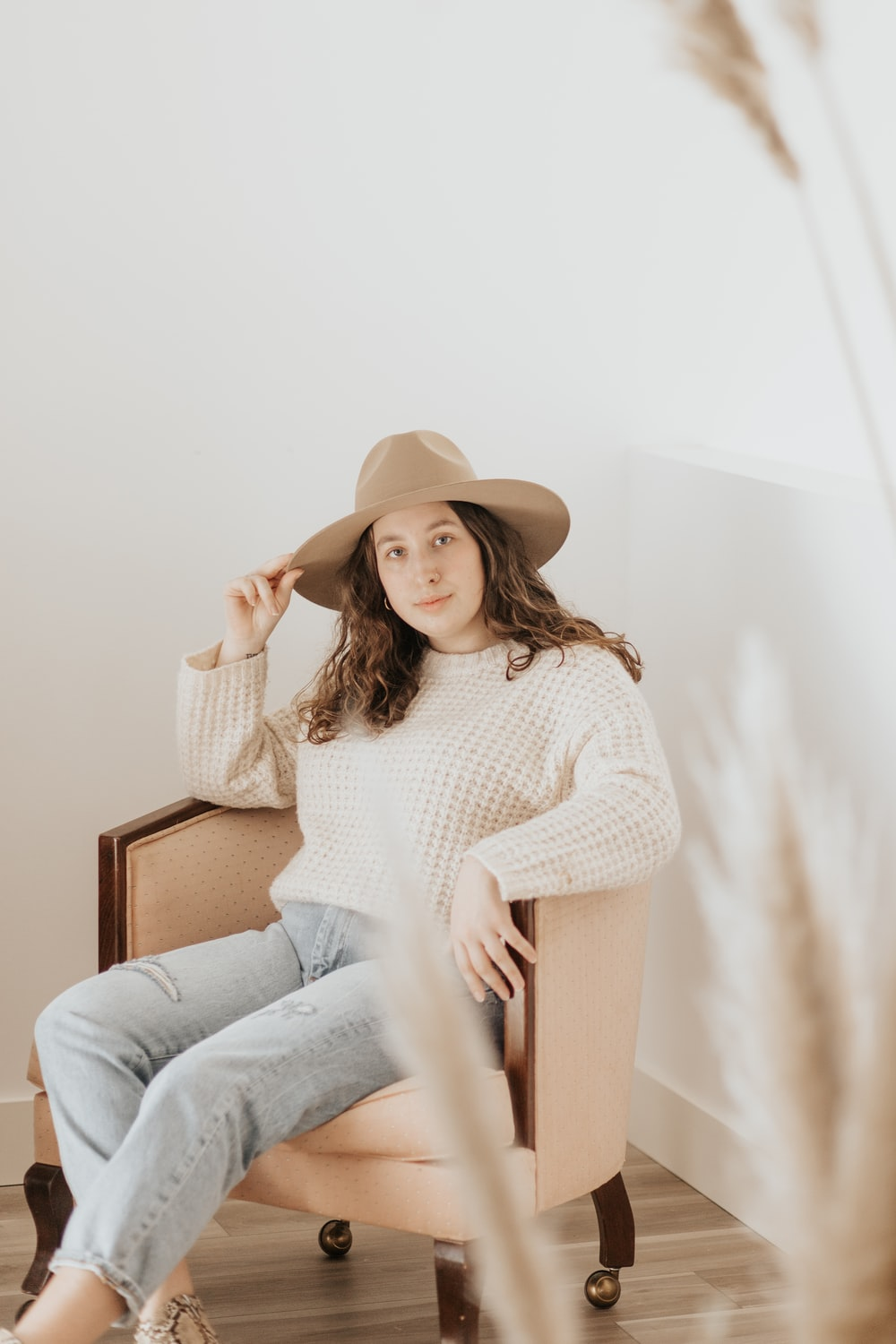 woman in white long sleeve shirt and blue denim jeans sitting on brown wooden chair