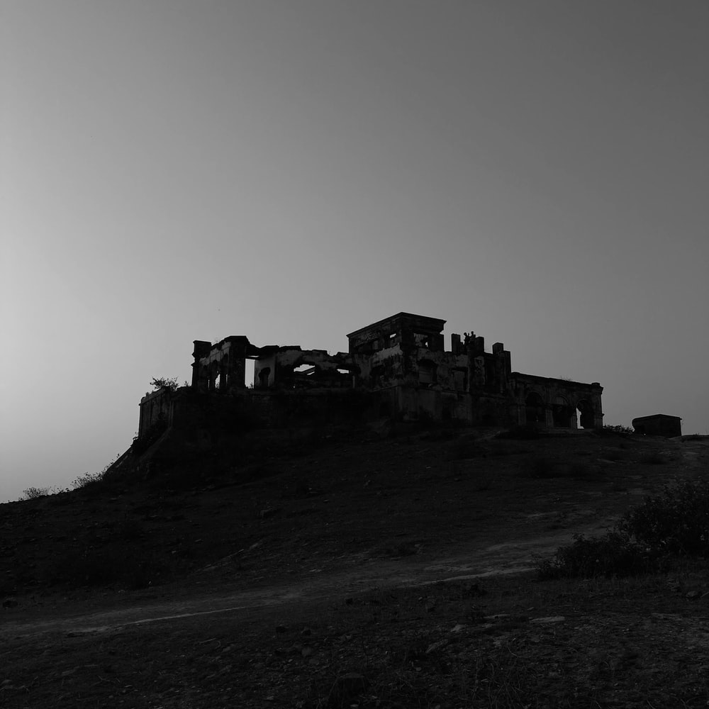 grayscale photo of building on hill