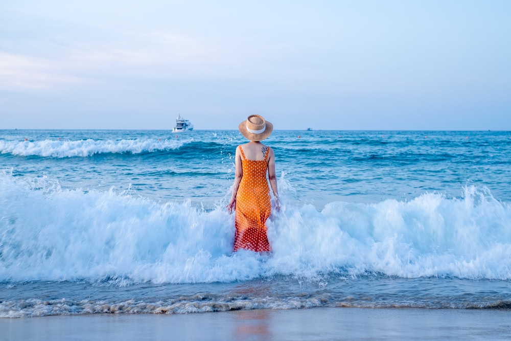 woman in orange dress standing on beach during daytime