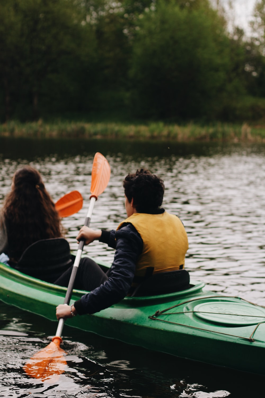 woman in yellow and black jacket riding green kayak on lake during daytime