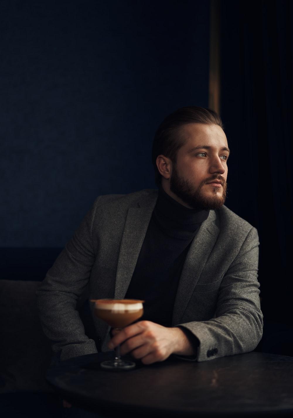 man in gray suit jacket holding brown ceramic mug
