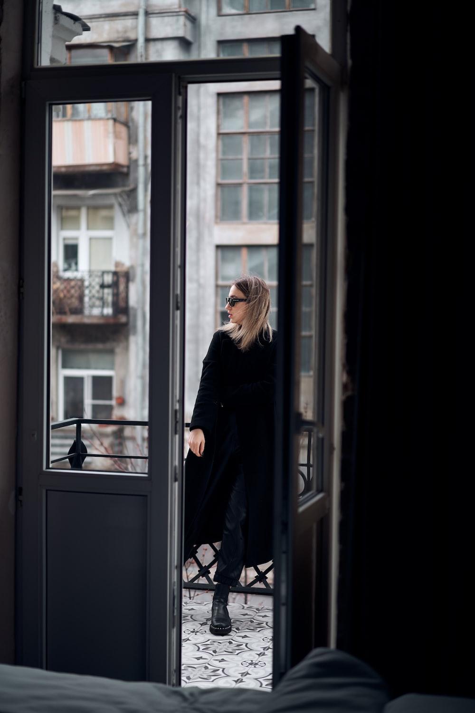 woman in black coat standing in front of glass window