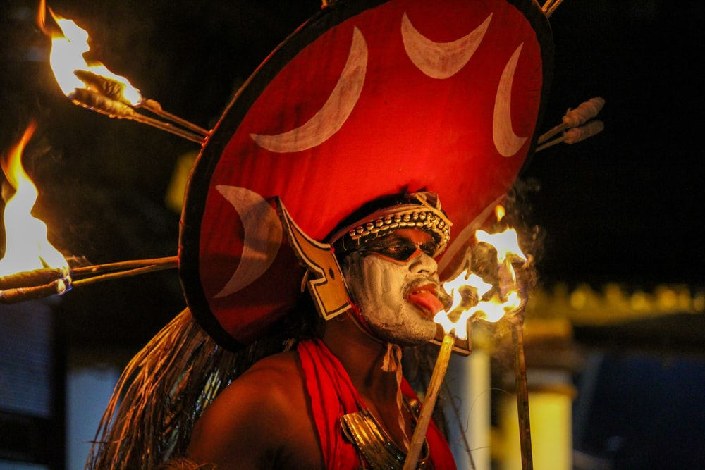 man in red and gold costume holding a stick