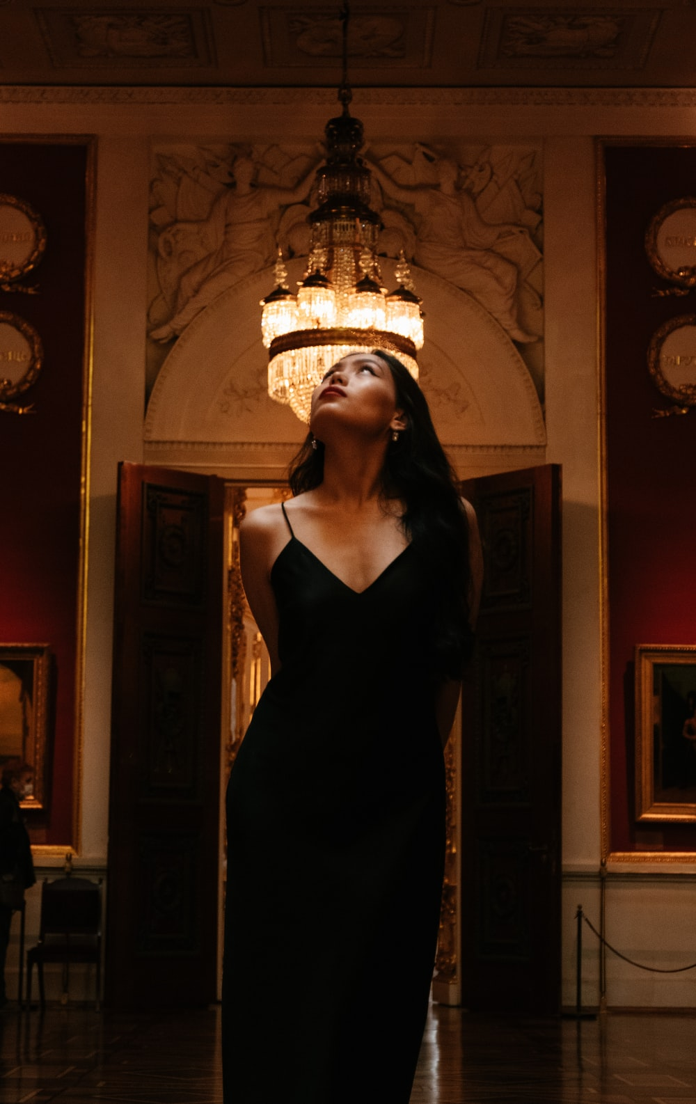 woman in black spaghetti strap dress standing near brass framed wall mirror