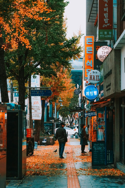 man in black jacket walking on sidewalk during daytime
